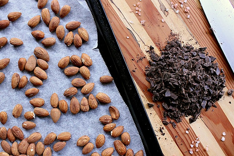 Baking sheet with roasted almonds next to a pile if chopped chocolate.