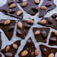 Keto Almond Bark broken into pieces, on parchment paper.
