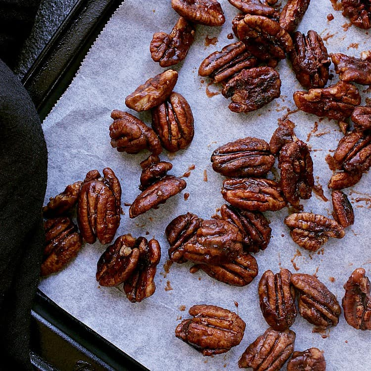 Baking sheet with parchment paper and sugar free candied pecans.