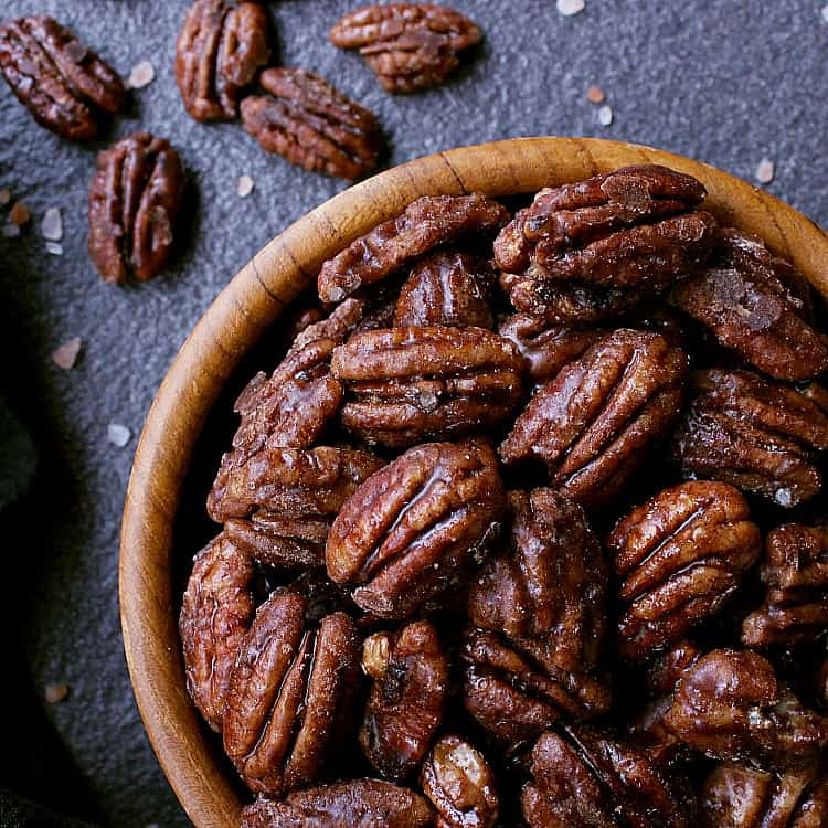 Wooden bowl of sugar free candied pecans on a stone surface.