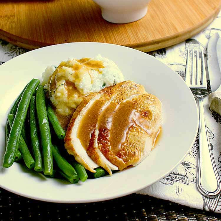Plate with chicken, green beans and mashed cauliflower, all covered in keto gravy.