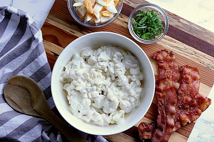 Cutting board with a bowl of cauliflower mixed with dressing, bowl of diced eggs, bowl of green onion and some crispy bacon.