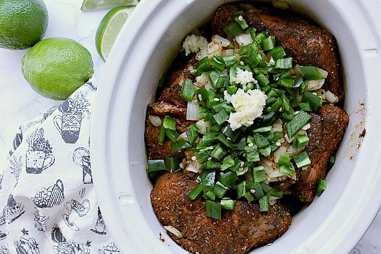 Slow cooker with pork and chopped veggies.
