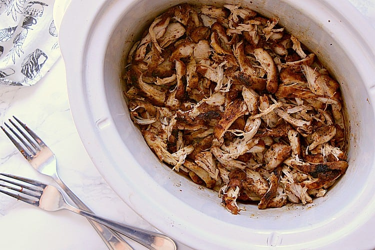 Slow cooker with shredded chicken.