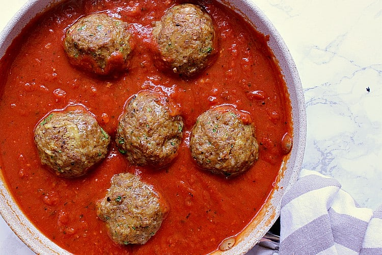 Saucepan with marinara sauce and cooked meatballs.
