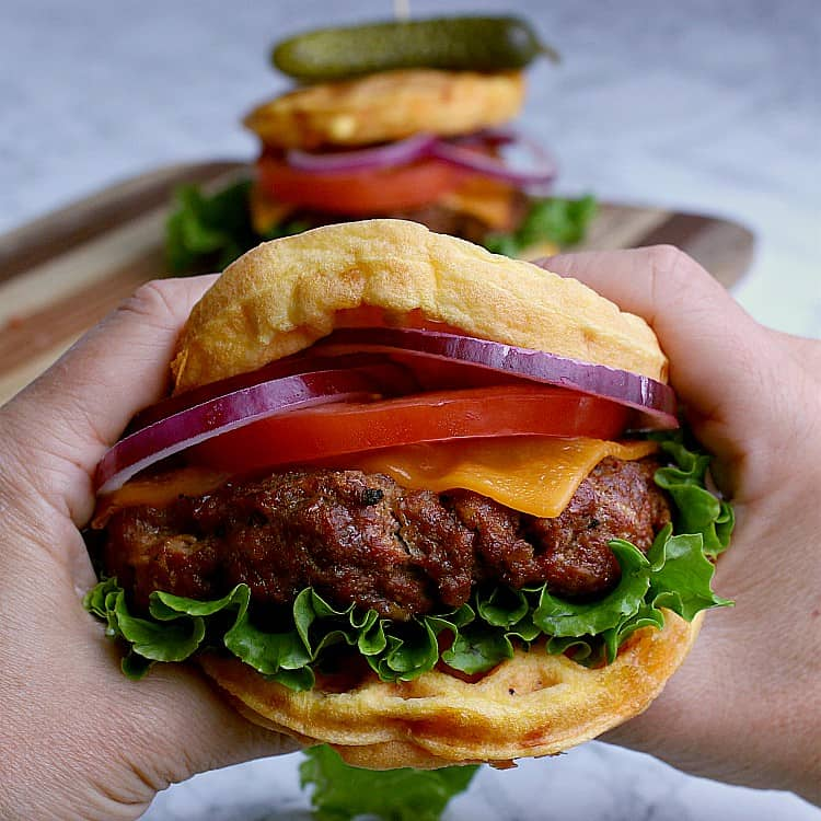 Holding up a fully loaded keto burger, loaded with lettuce, cheese, tomato and red onion, held together with two chaffles.