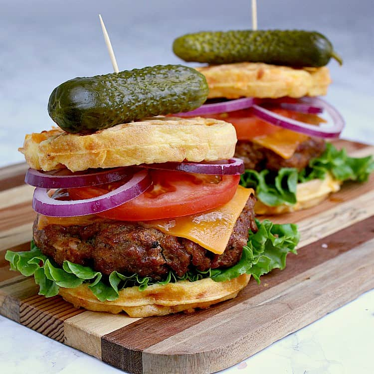 Two keto burgers loaded with cheese, tomato, red onion and lettuce, both on chaffles and placed on a wood cutting board.