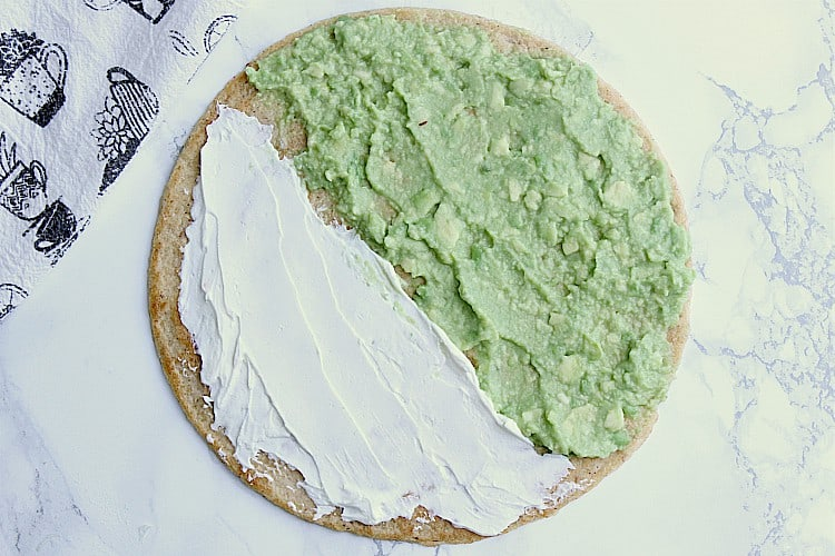tortilla with mashed avocado on one side and cream cheese on the other.