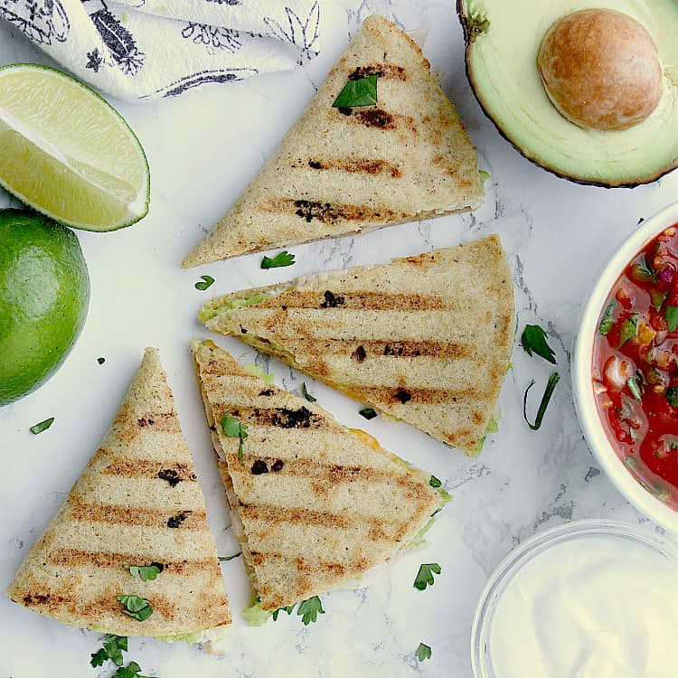 Keto Quesadilla sliced into 4 wedges next to lime wedges, half an avocado, a bowl of salsa and sour cream.