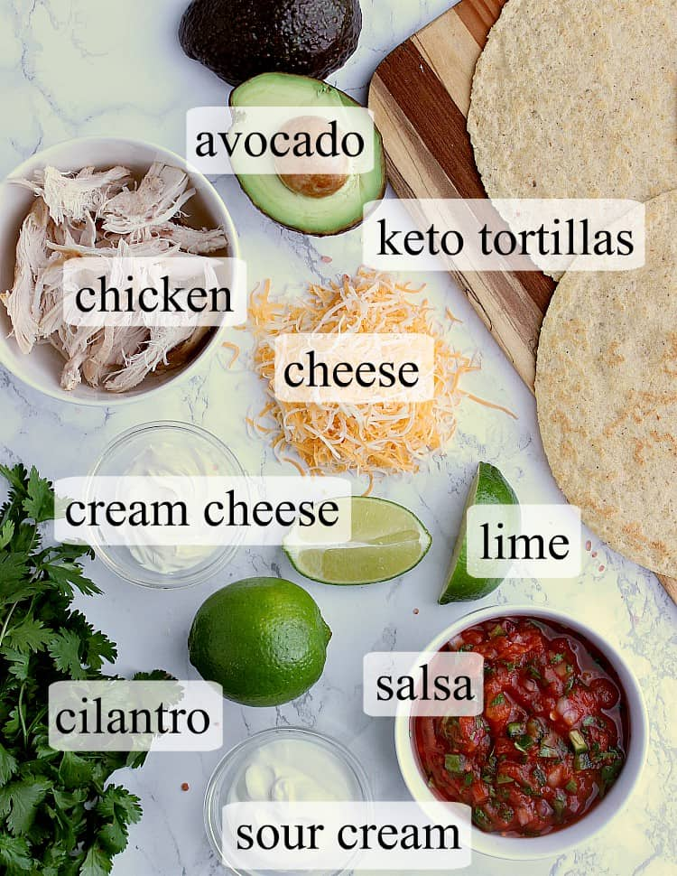 All ingredients used in this Keto Quesadilla - almond flour tortillas, an avocado, shredded chicken, shredded cheese, a lime, cream cheese, bunch of cilantro, salsa and sour cream.