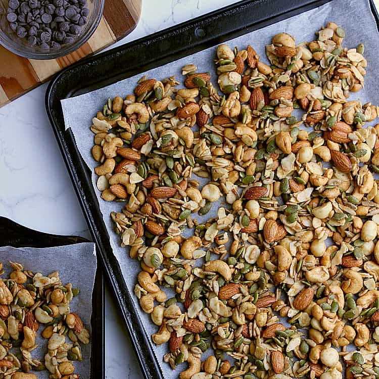 Two baking sheets with the prepared nuts and seeds, ready to be baked in the oven.