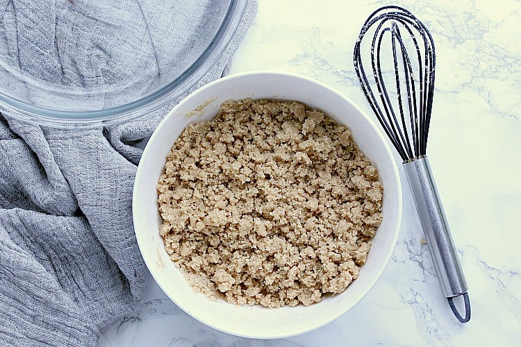 A white bowl with the pie crumbs made and ready to be placed inside the pie plate.