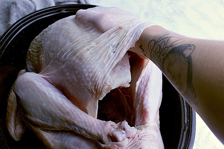 A hand in between the skin and breast of a turkey.
