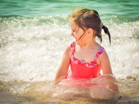 criança brincando na agua da praia