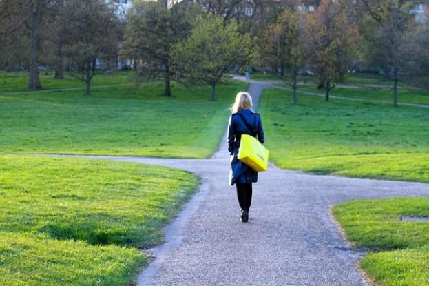 Frau steht an einer Wegkreuzung im Park