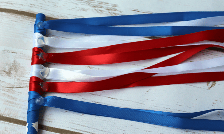 Work your hot-glue-gun magic and adhere the ribbons to the wand with a dot of glue. These patriotic ribbon wands will last through many parades and dance parties.