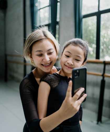 cheerful asian ballerinas taking selfie in ballet studio