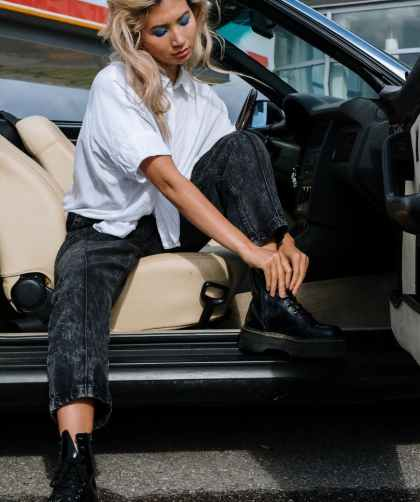 woman in white shirt and black denim jeans sitting on beige car seat