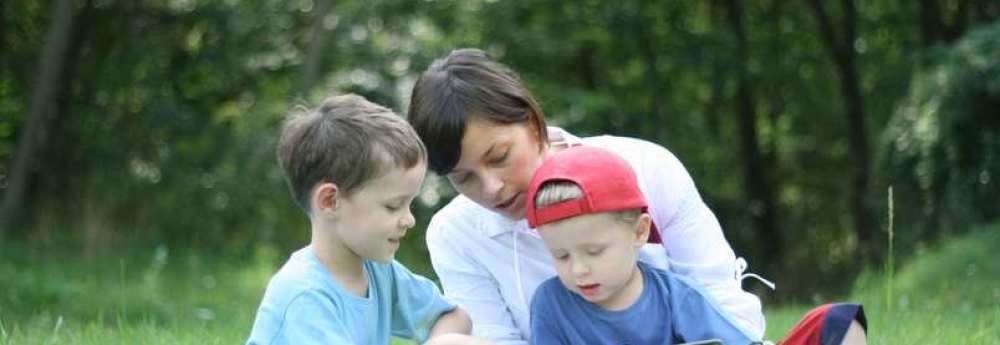 mother boys children lying grass reading outdoors - How to motivate your child to read - My Story