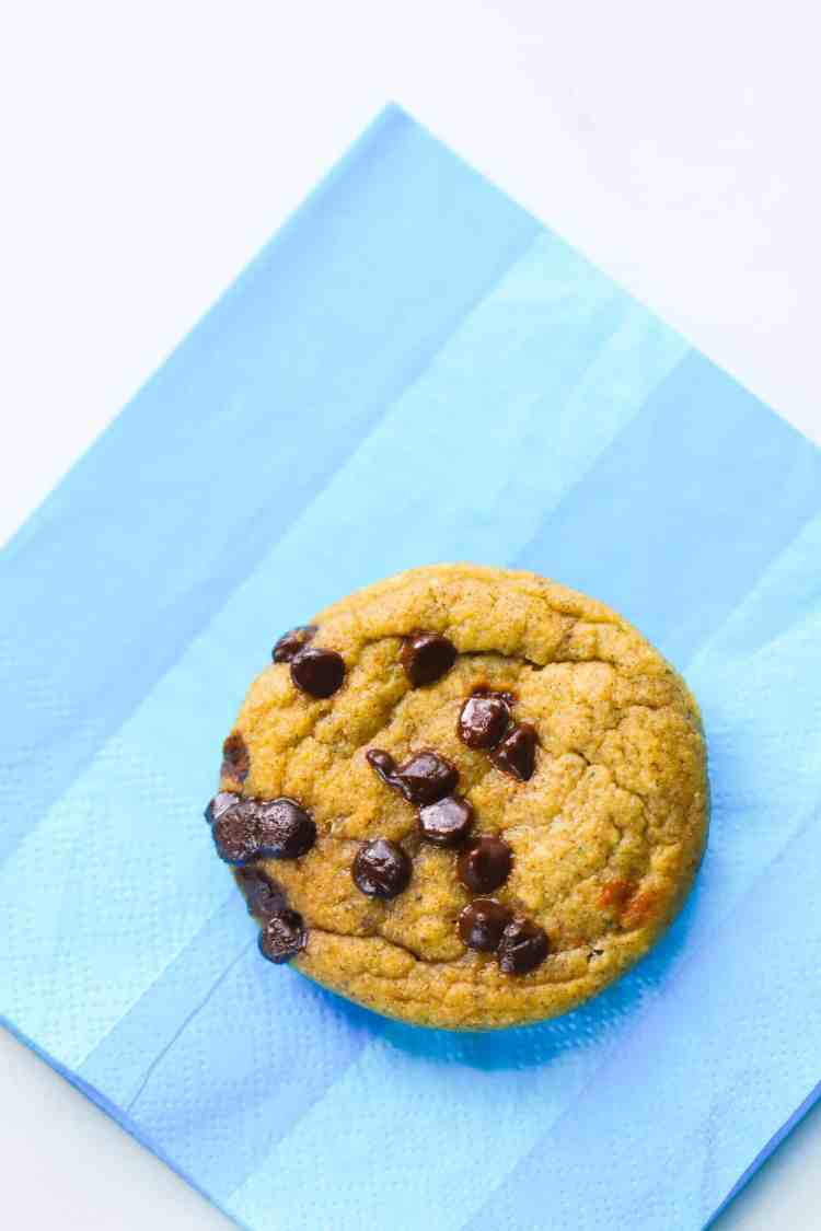 zucchini banana bread muffin with mini chocolate chips on a blue napkin