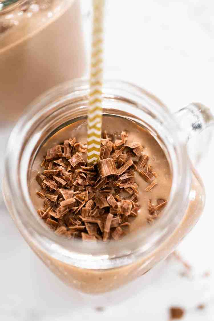 healthy chocolate smoothie recipe with chocolate shavings in a glass jar with white background