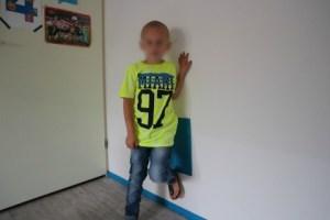 Vingino kleding voor de kinderen Luca voet tegen muur