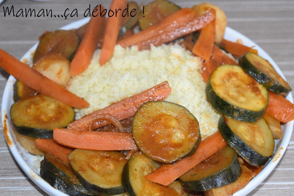 Mettre la semoule et les raisins dans un bol, mesurer la même quantité d'eau et la porter à ébullition. Hors du feu, ajouter l'huile d'olive et verser sur la semoule. Laisser gonfler pendant 15 à 20 minutes. Pendant ce temps, faire chauffer le bouillon de légumes dans un faitout. Parfumer avec le cumin et le ras-el-hanout. Verser les oignons (si comme moi vous utilisez un oignon traditionnel, faites-le revenir avant) et les carottes coupées en rondelles, laisser cuire 10 minutes à feu moyen. Couper les courgettes en rondelles, les ajouter et poursuivre la cuisson 15 minutes. Egoutter les pois chiches, les ajouter dans le faitout et faire réchauffer le tout 5 minutes. Au dernier moment, parsemer de coriandre. Mettre la semoule dans un plat creux en l'émiettant, l'entourer de légumes et mouiller avec un peu de bouillon. Donner un tour de moulin à poivre.