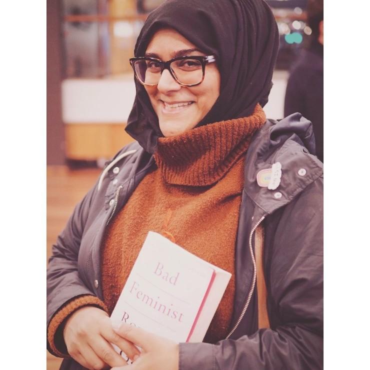 Aiysha Malik holding a copy of the book Bad Feminist by Roxane Gay