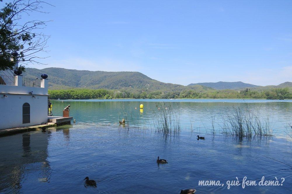 oficina de turismo de Banyoles y lago con patos, al fondo las montañas