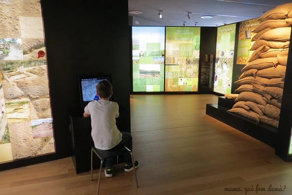 Niño mirando el ordenador interactivo del museo del Poblat ibèric Ca n'Oliver de Cerdanyola del Vallès