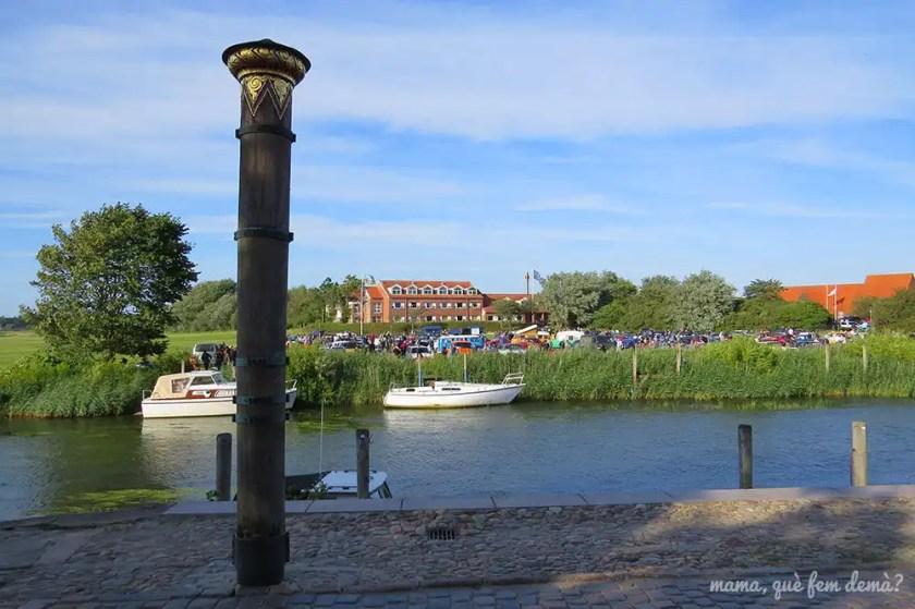 Columna Stormflodssøjlen en Ribe, con el rio de fondo y la feria de coches clásicos
