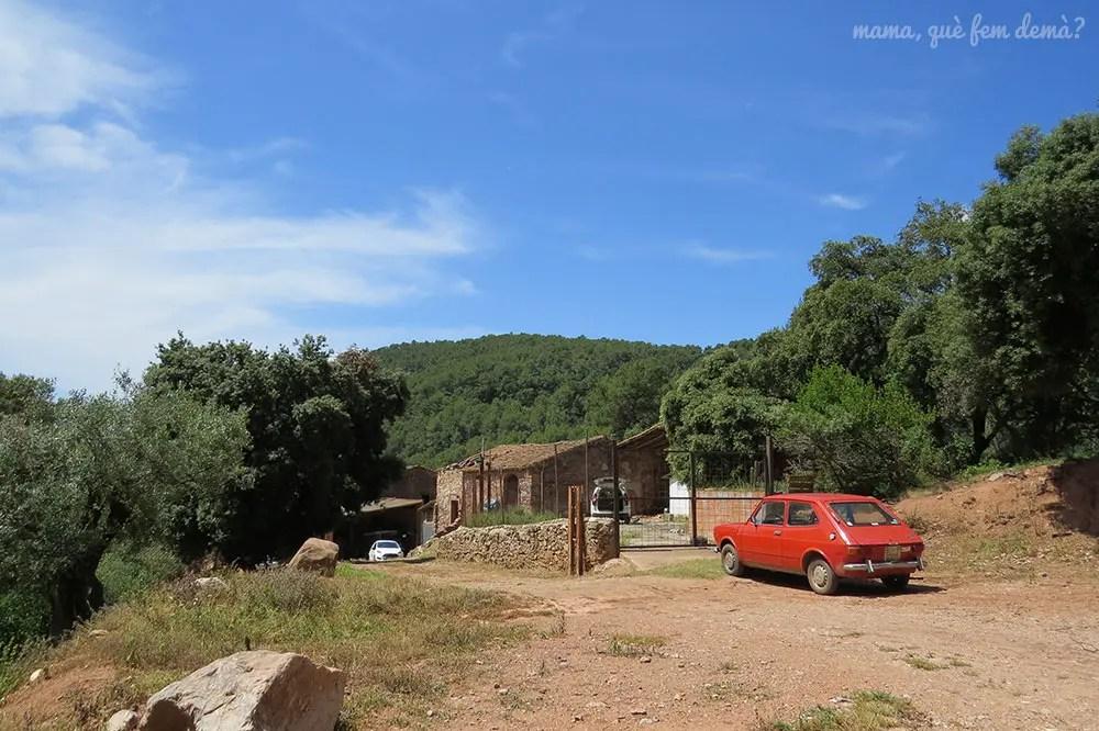 Coche antiguo aparcado delante de la masia Can senosa