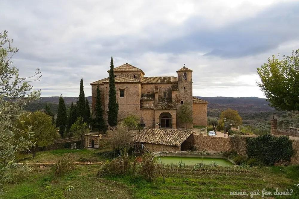 Parroquia de San Miguel Arcángel de Alquézar con huertos delante y las montañas detrás