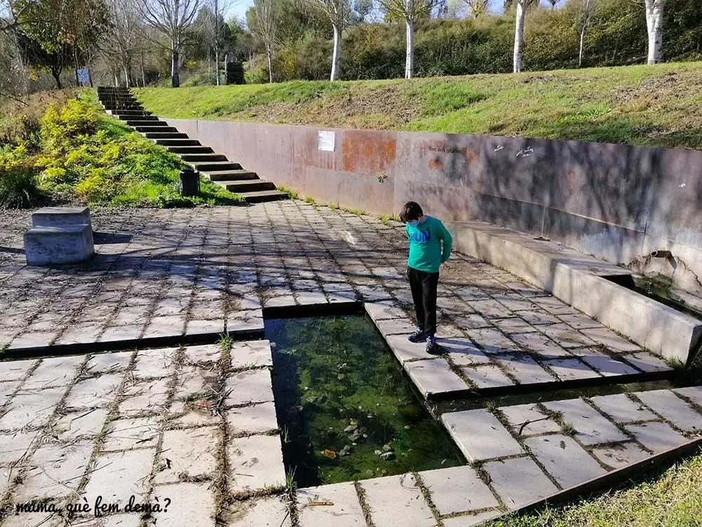 niño mirando el pequeño estanque de la font dels gitanos de sabadell