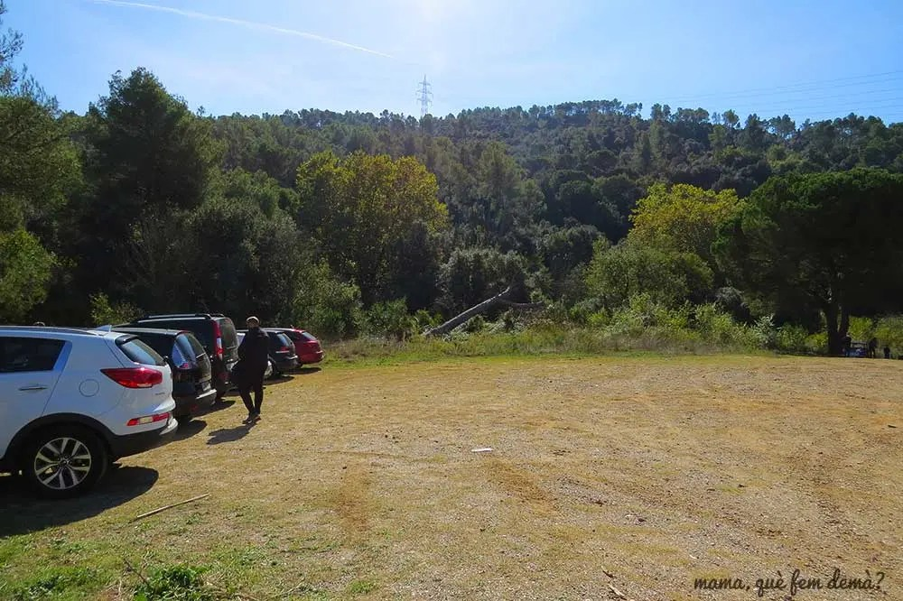 Coches aparcados en el aparcamiento de tierra de la Rierada en Molins de Rei