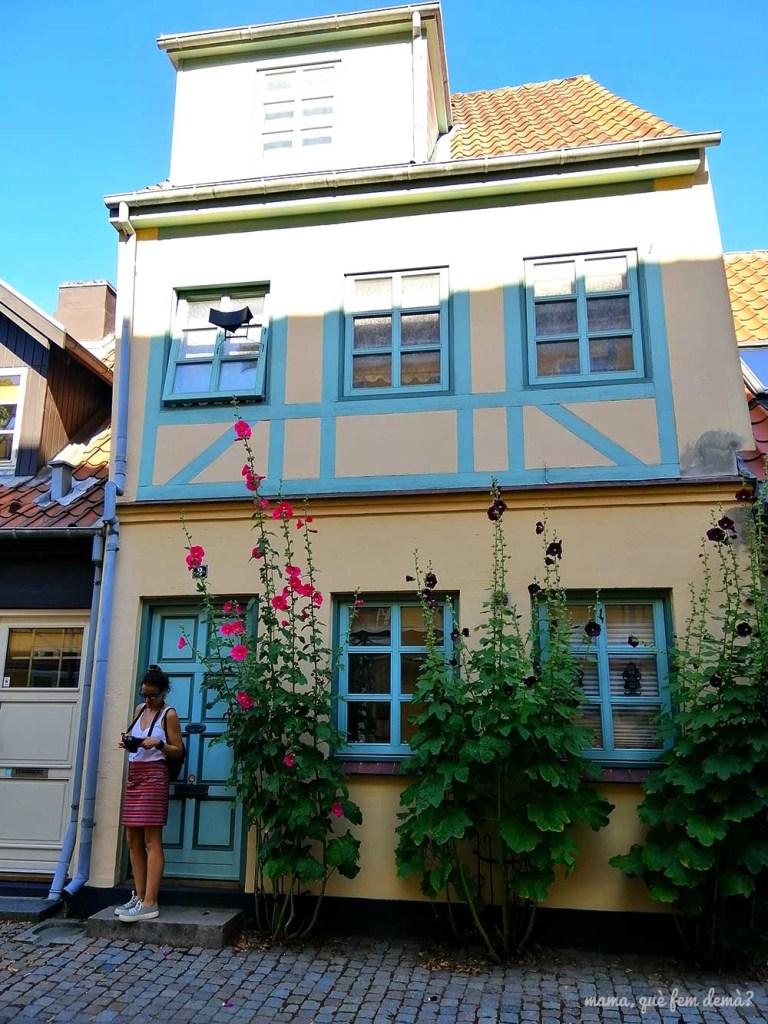 Mujer delante de una casa de entramado con flores en la puerta en Odense, Dinamarca