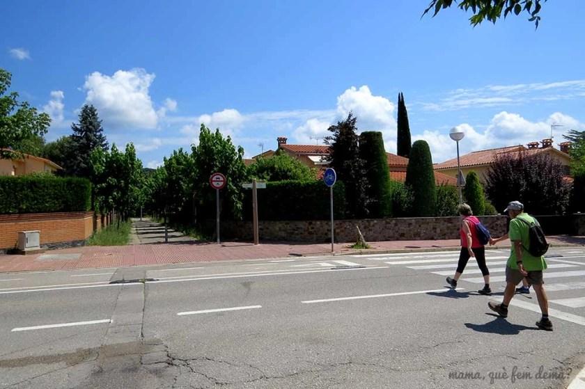 Tres personas cruzando la carretera hacia la calle Europa de Santa Maria de Palautordera