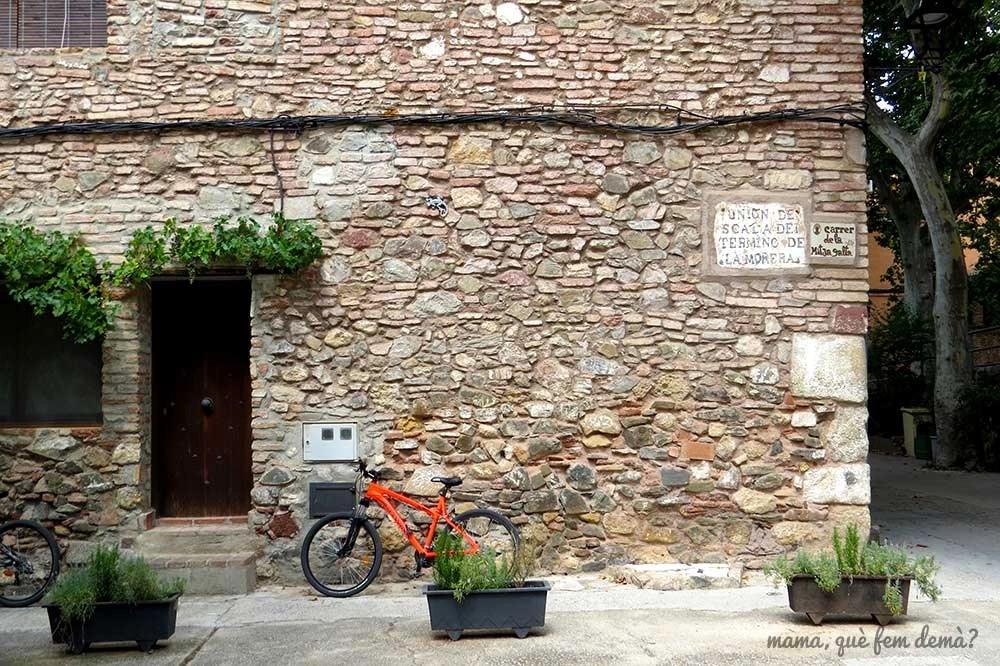 Pared de piedra con una bici apoyada en el pueblo de Escaladei