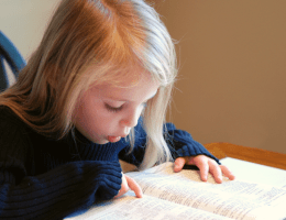 girl reading Bible. Bible memory verses for kids feature image.