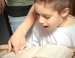 Mom pointing out a Bible verse to excited son.