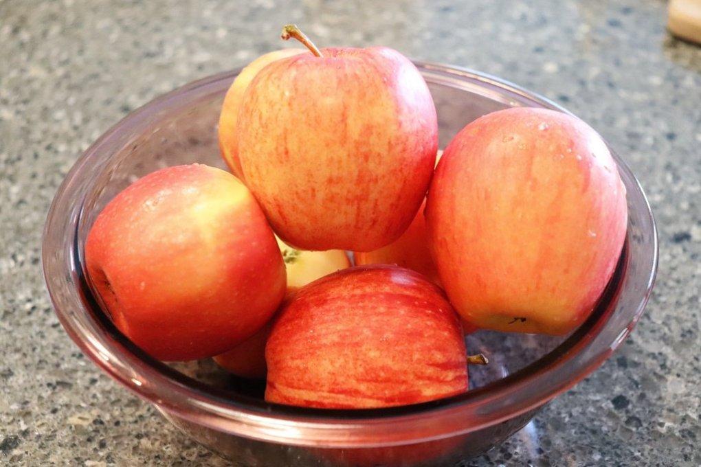 Manzanas rojas en el mesón de la cocina. Postre de manzana con canela en la olla instantánea
