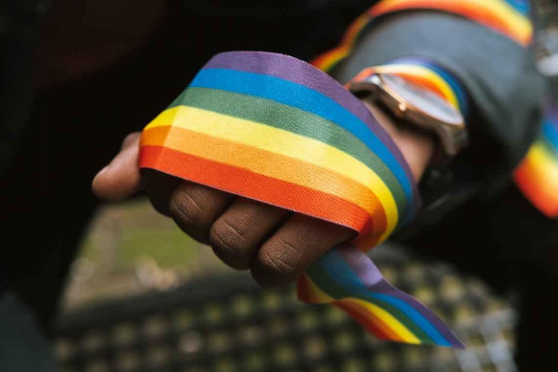 crop faceless black gay demonstrating rainbow ribbon on hand