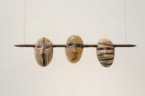 Installation of three head shaped sculptures on a rod