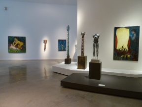 Installation shot of sculptures and paintings in a museum
