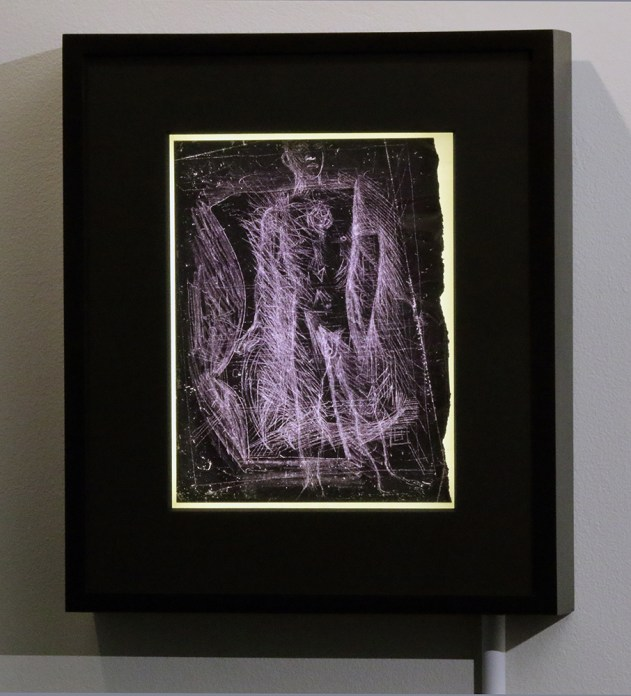 Installation shot of a carbon paper drawing displayed in a lightbox