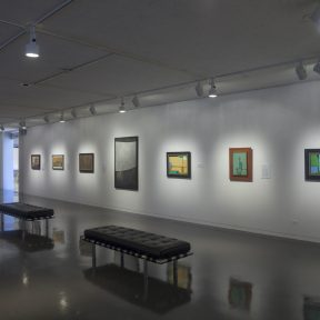 Installation shot of paintings on a wall in a museum
