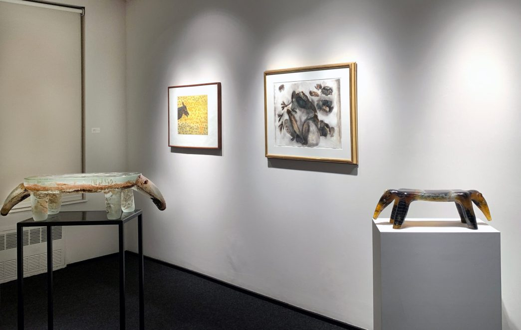 Installation shot of two glass sculptures of anteaters in the front gallery