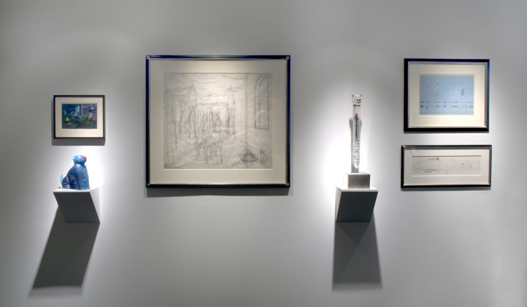 Picture of a wall with four hanging artworks and two small sculptures