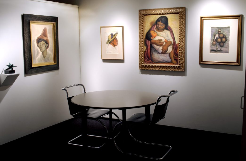 Picture of a corner of the booth with five artworks hanging on the walls and one round table in the middle