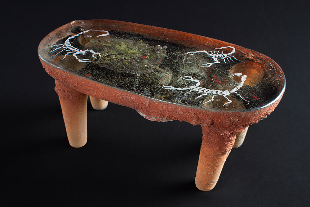 Glass sculpture shaped like a pre-Columbian metate with scorpions engraved on top